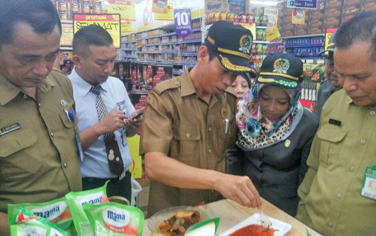 Ketua DPRD Kobar Triyanto dan anggota DPRD Kobar Sri Lestari didampingi Kadisperindagkop mengecek makanan kaleng ikan