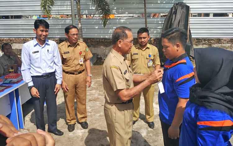 Staf Ahli Bupati Kotim, Arnila, saat memasang pita kepada perwakilan peserta pendidikan dan pelatihan kerja.