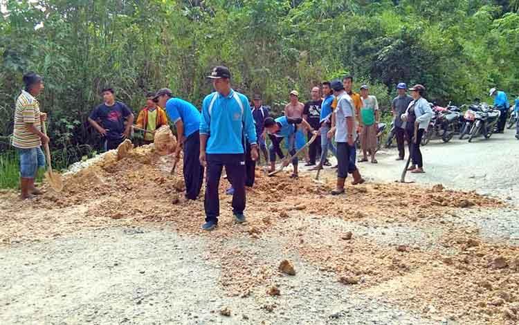 Warga masyarakat Desa Trahean dan Trinsing, Kecamatan Teweh Selatan, Kabupaten Barito Utara, bergotong royong memperbaiki jalan rusak menuju desa mereka, Senin (16/4/2018).