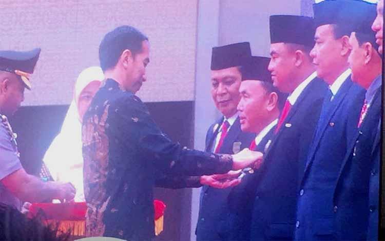 Presiden Joko Widodo menyematkan tanda penghargaan kepada Gubernur Kalteng, Sugianto Sabran