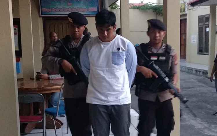 Tersangka (baju putih) dijaga oleh anggota Polisi bersenjata lengkap saat berada di Mako Polres Kotim