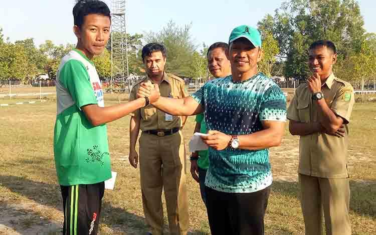 Kerua KONI Sukamara, M Yamin saat memberikan bonus kepada atlet salah satu cabang olahraga.