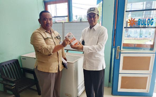 Kepala Bulog Sub Divre Muara Teweh Abdul Azis (kiri) memperlihatkan daging sapi beku kemasan 1 kilogram kepada anggota DPR RI Hamdhani, Senin (15/10/2018).