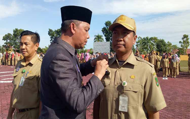 Bupati Sukamara, Windu Subagio menyematkan PIN Melayani Dengan Ikhlas kepada salah satu perwakilan ASN