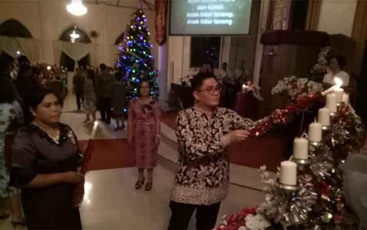 Wakil Bupati Gumas Rony Karlos menyalakan lilin saat Perayaan Natal SPPer Jemaat GKE Sion di Gereja Sion, Kamis (6/12/2018) malam.