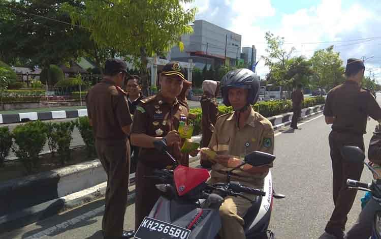 Jajaran Kejari Kapuas saat membagi stiker anti korupsi kepada warga yang melintas di Jalan A Yani.