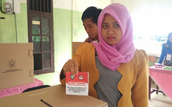Seorang warga menunjukkan surat suara yang sudah dicoblos dan akan dimasukan kedalam kotak suara pada pilkades, Minggu (16/12/2018).