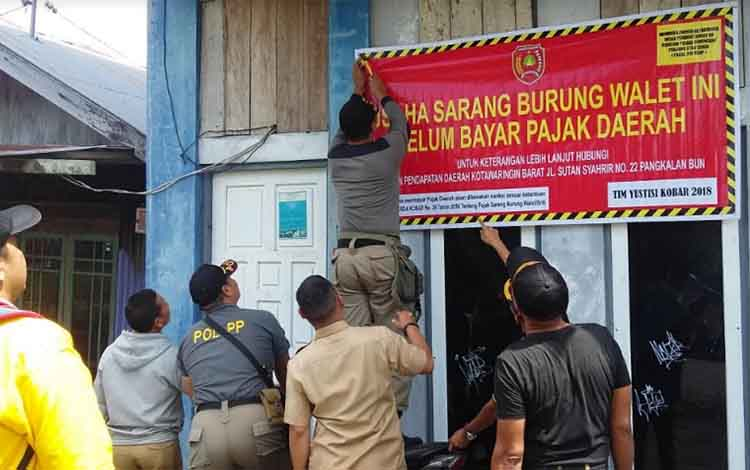 Petugas Bapenda dan Satpol PP Kobar memasang spanduk peringatan di bangunan penangkaran sarang burung walet, Selasa (15/12/2018).