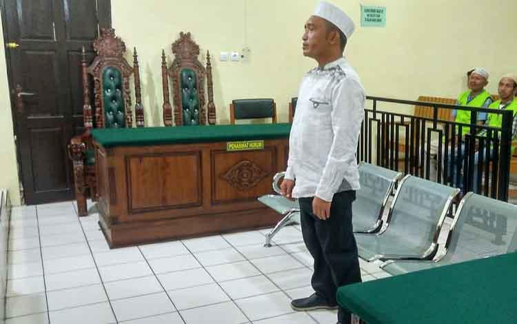 Terdakwa Ahmad Husaini mendengar putusan hakim saat sidang di Pengadilan Negeri Palangka Raya