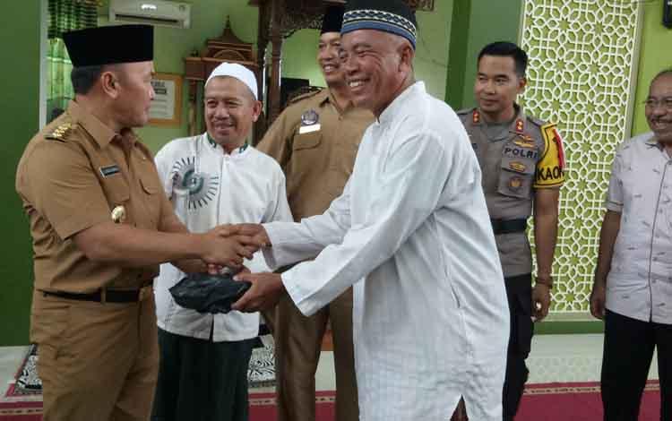 Gubernur Kalteng Sugianto Sabran menyerahkan bantuan kepada pengurus masjid.
