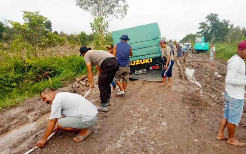 Bakti sosial perbaikan jalan rusak oleh Polsek Sebangau Kuala dan masyarakat.