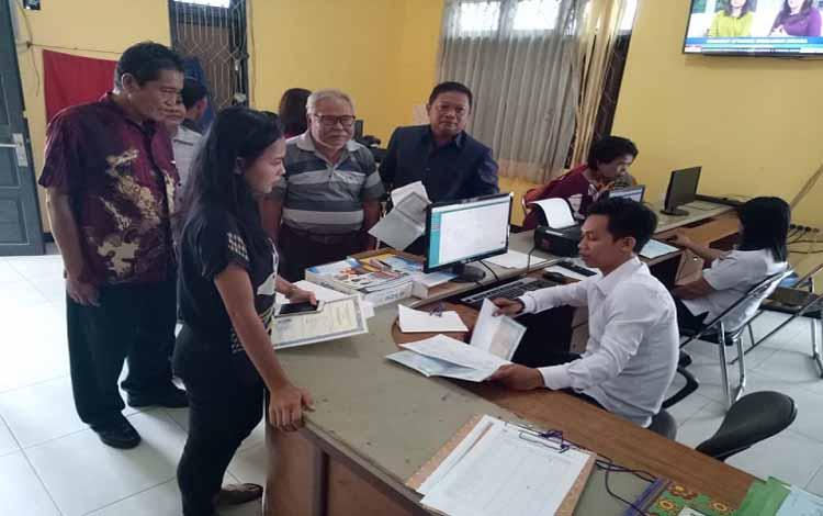 Anggota DPRD Gunung Mas, Iswan B Guna (kanan) mengantar keluarga mengurus administrasi kependudukan