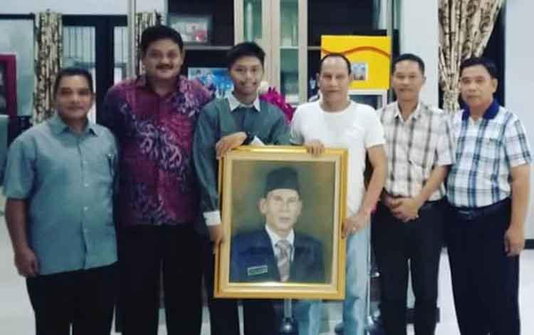 Pelajar SMAN 1 Kurun Ilham Fahmi Ali menyerahkan langsung lukisan wajah Bupati Gumas yang diterima langsung Bupati Gumas Arton S Dohong.