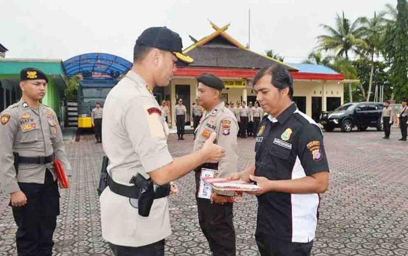 Kapolres Barito Utara menyerahkan penghargaan kepada dua personel berprestasi.