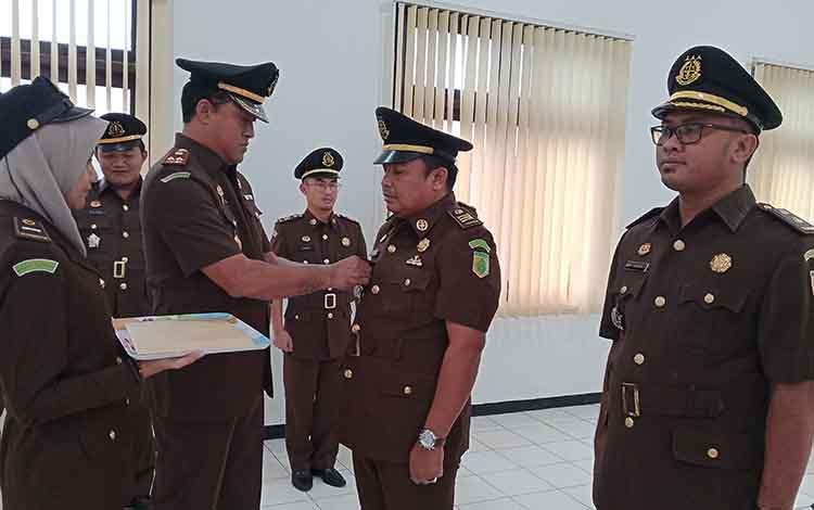 Kejari Kotim Wahyudi menyematkam tanda jabatan Kasi Intelijen baru, Sunardi Ependi.