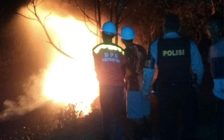 Petugas pemadam kebakaran sedang berupaya memadamkan klotok yang terbakar, Selasa (29/1/2019) malam.