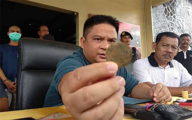 Kapolres Kotim AKBP Mohammad Rommel menunjukkan koin emas palsu yang digunakan pelaku untuk melancarkan aksinya