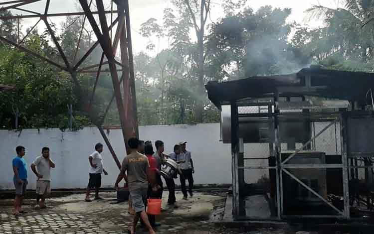 Anggota Polsek dan warga saat memadamkan  api yang membakar gardu tower seluler di Desa Bawan.
