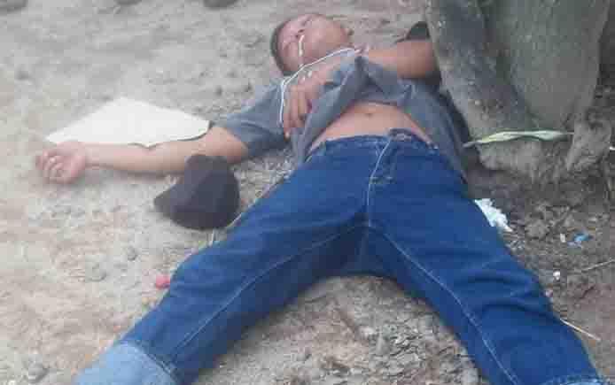 Pemuda terkapar di pinggir jalan.