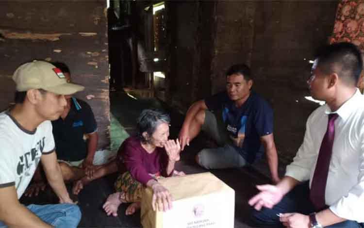 Kasat Reserse Narkoba Polres Pulang Pisau Iptu Purnomo menyerahkan bantuan kepada wanita tua sebatang kara di Pulang Pisau.
