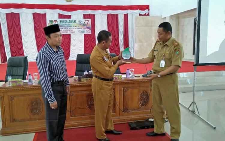 Sekda Sukamara Sutrisno (tengah) menerima plakat dari pejabat Pemprov Kalimantan Tengah saat sosialisasi partisipasi pemilih Pemilu 2019.