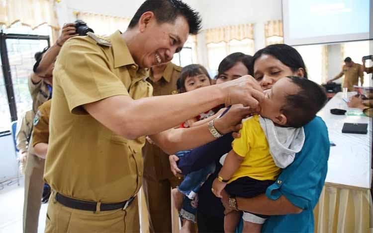 Bupati Barito Utara, Nadalsyah memberikan vaksin vitamin A kepada anak