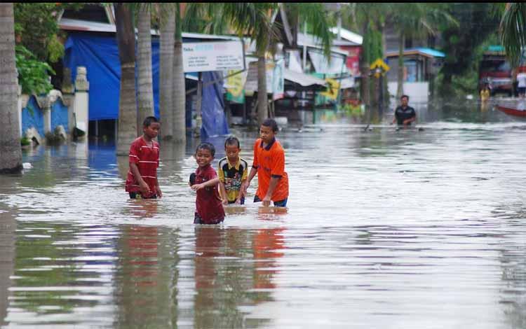 Anak-anak yang sedang bermain di lokasi banjir