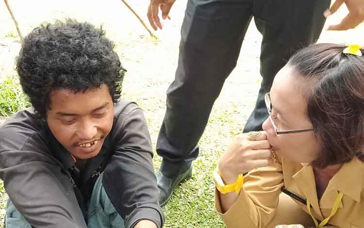 Petugas dari dinas sosial membujuk laki-laki (kiri) yang diduga mengalami gangguan jiwa, Selasa (12/2/2019).