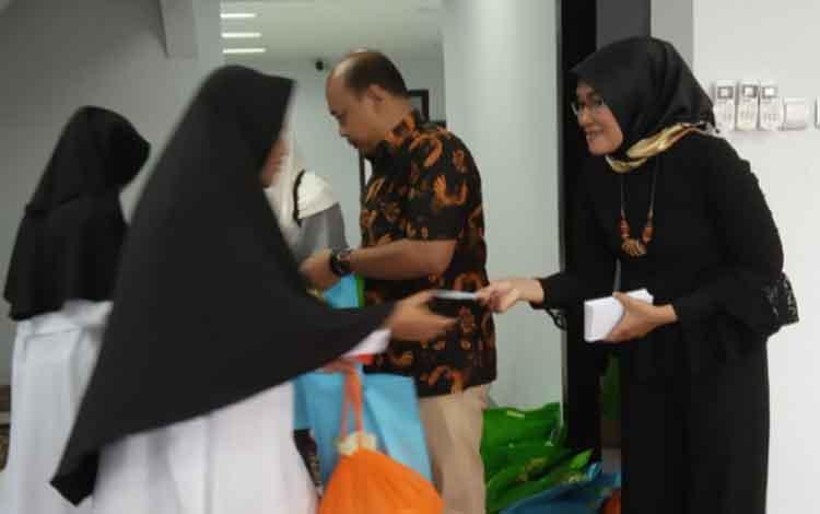 Pimpinan Perusahaan Borneonews- Palangka Post, Revi Apriani memberikan tali asih pada santri Dar Ar-Raudhah usai syukuran menempati kantor baru.
