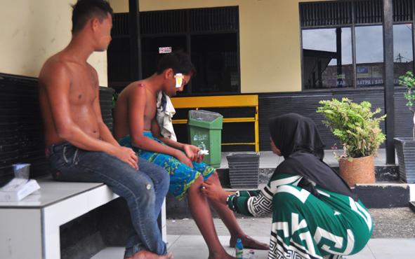 Seorang ibu sedang merawat anaknya yang mengalami luka di pipi dan kedua lututnya, Minggu (24/2/2019).