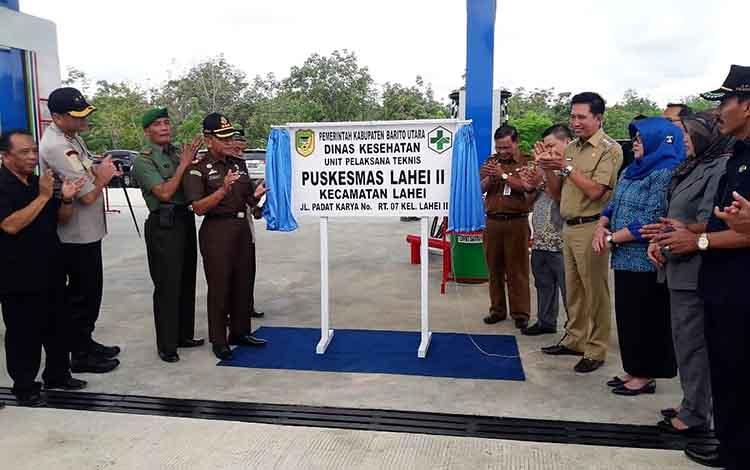 Bupati Barito Utara H Nadalsyah saat membuka tirai papan nama Puskesmas tanda diresmikannya Puskesmas.