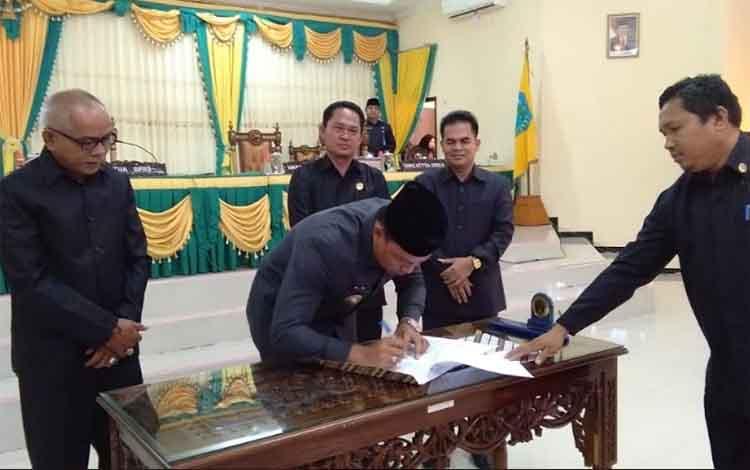 Bupati Lamandau Hendra Lesmana saat menandatangani berita acara persetujuan raperda RPJMD dalam sidang paripurna, Senin (25/2/2019).