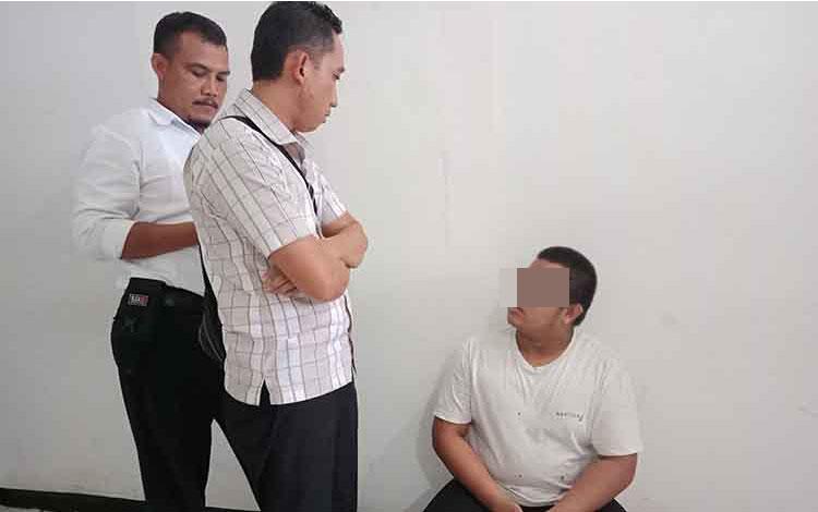 AR alias Amd (duduk)  terdakwa kasus cabul saat bersama penyidik.
