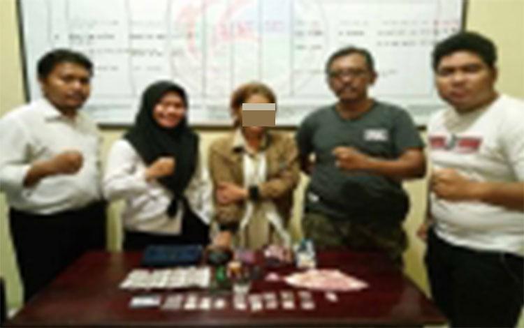 LM (34) ibu rumah tangga yang diamankan karena jadi bandar narkoba diapit anggota Satresnarkoba