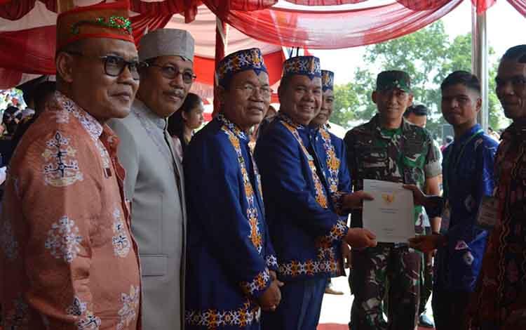 Bupati Kapuas Ben Brahim S Bahat menyerahkan secara simbolis sertifikat didampingi Kepala Kantor BPN Kapuas Suraji (paling kiri) di Stadion Panunjung Tarung