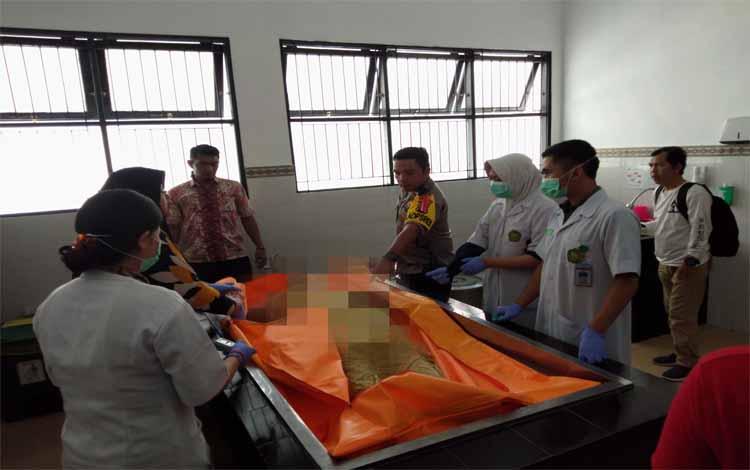 Kapolres Palangka Raya AKBP Timbul Rein Krisman Siregar bersama tim forensik mengecek tubuh korban, Jumat (22/3/2019)