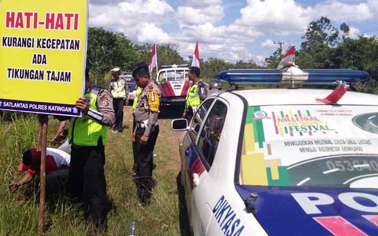 Anggota Satlantas Polres Katingan memasang spanduk imbauan daerah rawan lakalantas.