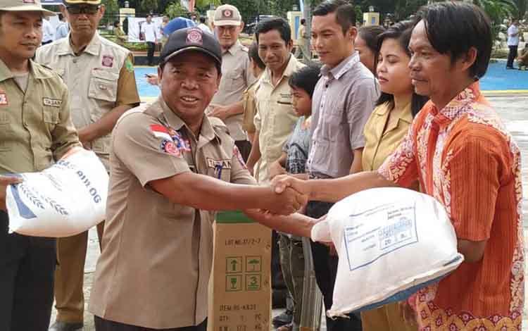 Kepala Dinas Sosial Pulang Pisau Satria During saat menyerahkan Rastra kepada masyarakat,  Senin (8/4/ 2019)