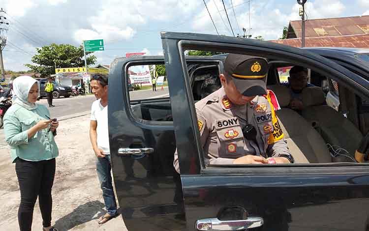 Kapolsek Pahandut AKP Sony Rizky Anugrah mengecek barang bawaan pengendara, Rabu (10/4/2019).