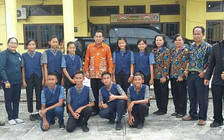 Kepala Dinas Pendidikan dan Kebudayaan Kabupaten Gunung Mas HM Rusdi bersama sejumlah Kepala Sekolah dan pelajar yang mewakili Kabupaten Gumas pada ajang OSN SMP tingkat Provinsi.