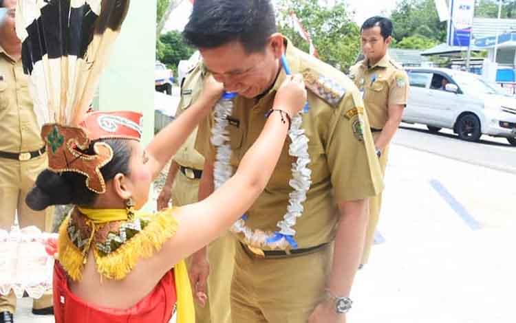 Bupati Barito Utara Nadalsyah mendapat kalungan bunga dari penari adat saat menghadiri Rakor Pemdes dan BPD se-Kecamatan Gunung Timang, Senin (15/4/2019).