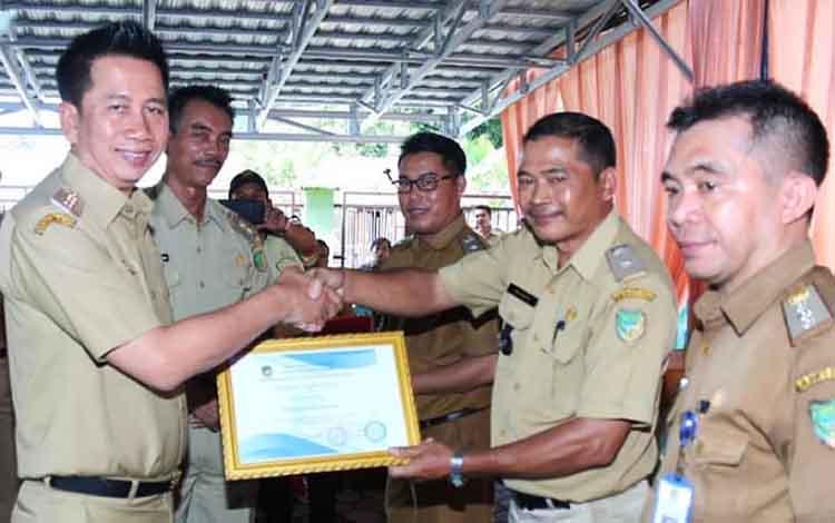 Bupat Barito Utara Nadalsyah saat menyerahkan piagam penghargaan kepada kepala desa pada Rakor Pemdes dan BPD se-Kecamatan Gunung Timang,Senin (15/4/2019).