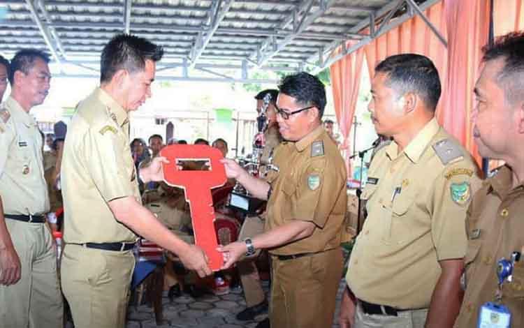 Bupati Barito Utara Nadalsyah saat menyerahkan secara kunci kendaraan secara simbolis kepada kepala desa pada Rakor Pemdes dan BPD se-Kecamatan Gunung Timang,Senin (15/4/2019).