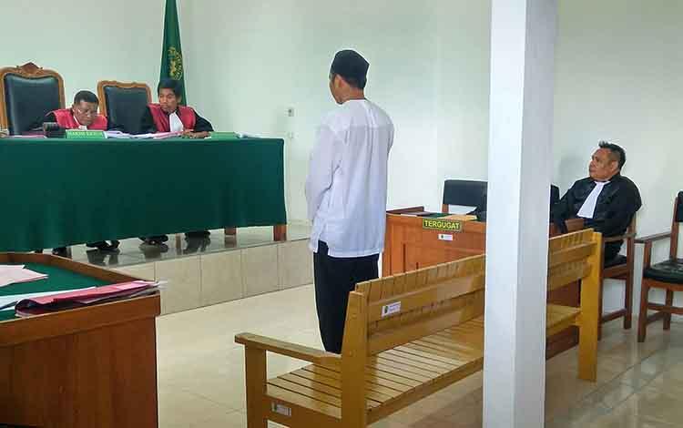 Fad berdiri mendengarkan amar putusan majelis hakim saat persidangan di Pengadilan Negeri Palangka Raya