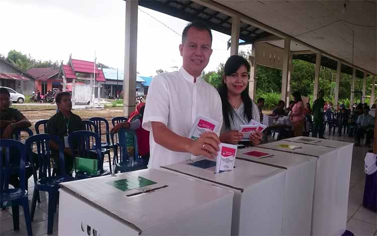Bupati Gunung Mas terpilih Jaya S Monong dan istri saat menggunakan hak pilih di TPS 26 Kelurahan Kuala Kurun