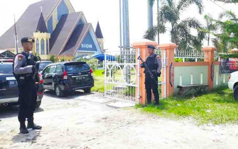 Polisi berjaga di depan gereja yang menggelar perayaan Paskah, Jumat (19/4/2019).