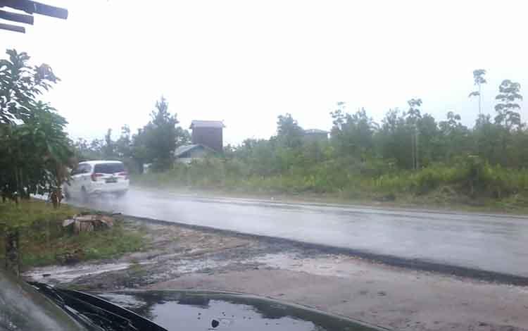 Sebuah mobil melaju saat hujan turun di Jalan Soekarno-Hatta Kasongan, Sabtu (20/4/2019).
