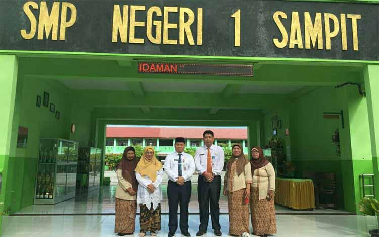 Sekda Kotim Halikinnor peci hitam bersama Kepala Dinas Pendidikan Suparmadi foto bersama dengan sejumlah guru di SMPN 1 Sampit