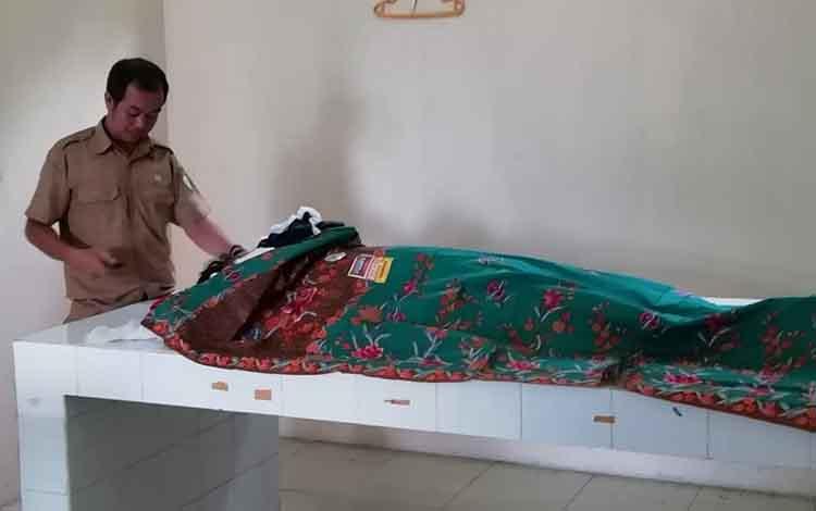 Kepala kamar jenazah RSUD dr Murjani Sampit, Kastro, sedang memeriksa jasad karyawab PT AWL, Senin, 29 April 2019.