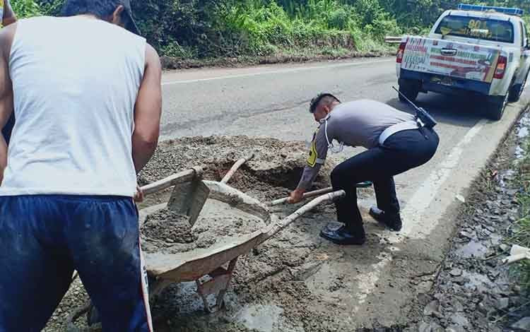 Kasat Lantas Polres Bartim Iptu Sugeng ditemani anggota menambal jalan berlubang di Jalan A.Yani Km 11 Tamiang Layang pada Selasa, 30 April 2019.